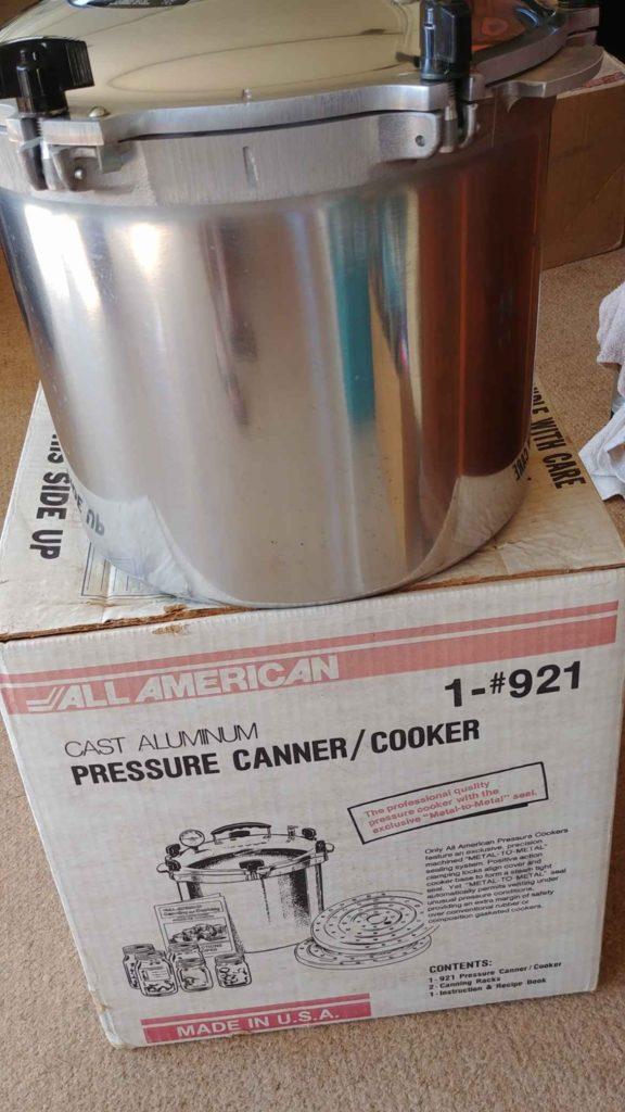 All American 921 Canner on top of its packaging